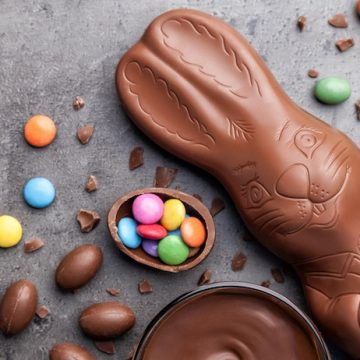 Chocolate Easter bunny and eggs on rustic background